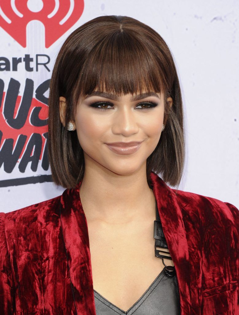 black hair bobs: close up shot of zendaya with scarface inspired bob hairstyle, wearing red velvet dress on the iHeartRadio Music Awards arrivals red carpet