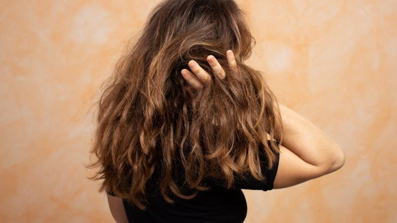Woman with dry hair touching it