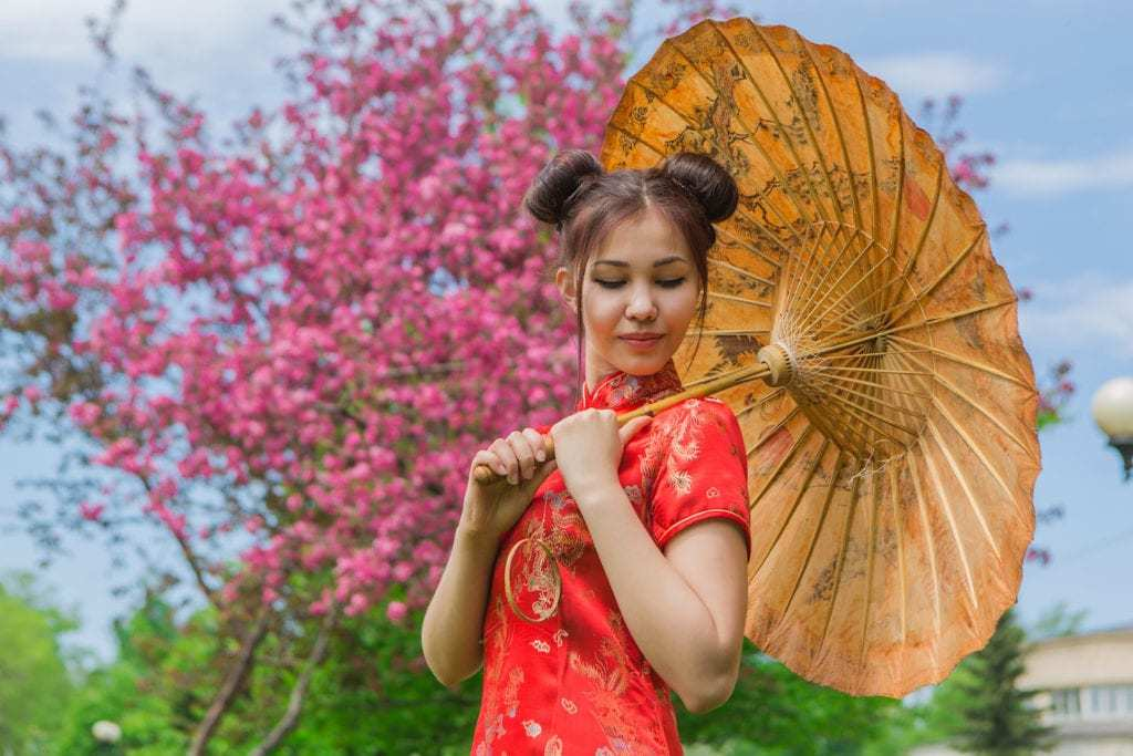 Asian hairstyles: Asian woman with brown straight hair in high donut space buns wearing traditional red outfit.