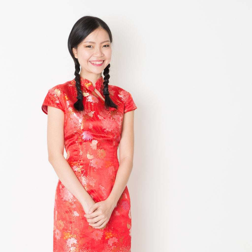Asian hairstyles: Asian model with brown straight hair in braided pigtails wearing red traditional floral outfit.