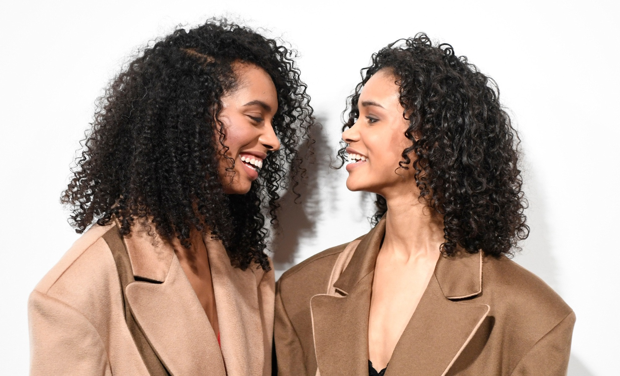 best shampoo for curly hair: close up shot of two women with curly hair, posing backstage at a fashion show