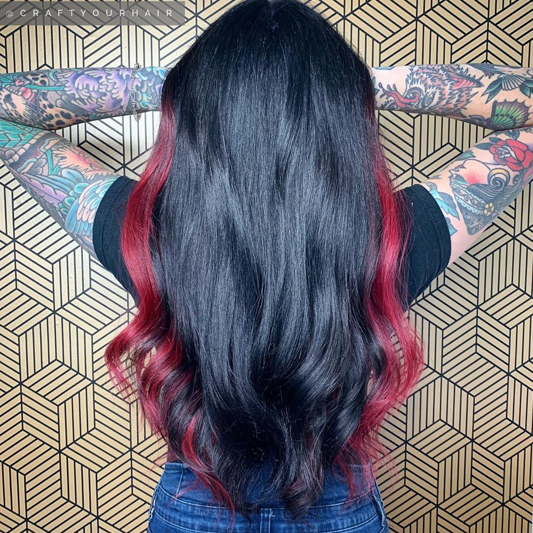 Woman with long black hair with red side highlights
