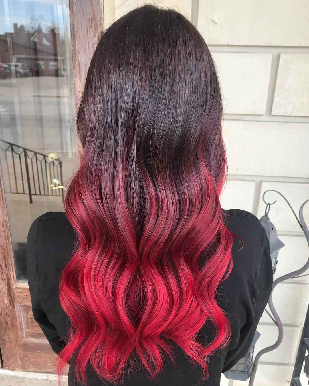 Woman with a black cherry hair colour done in an ombre technique on her long hair