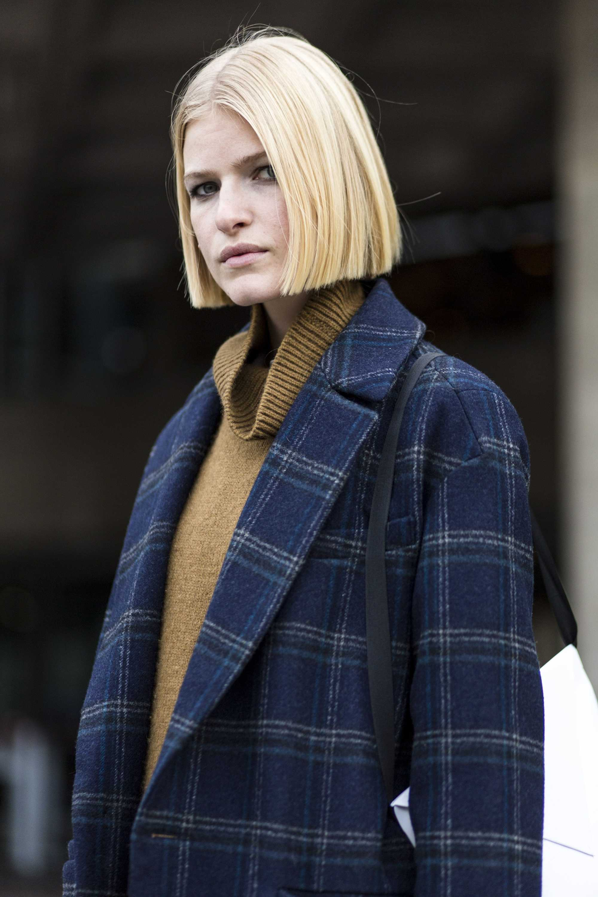 close up shot of woman with blonde blunt bob haircut, wearing blue jacket and mustard jumper at london fashion week 2018