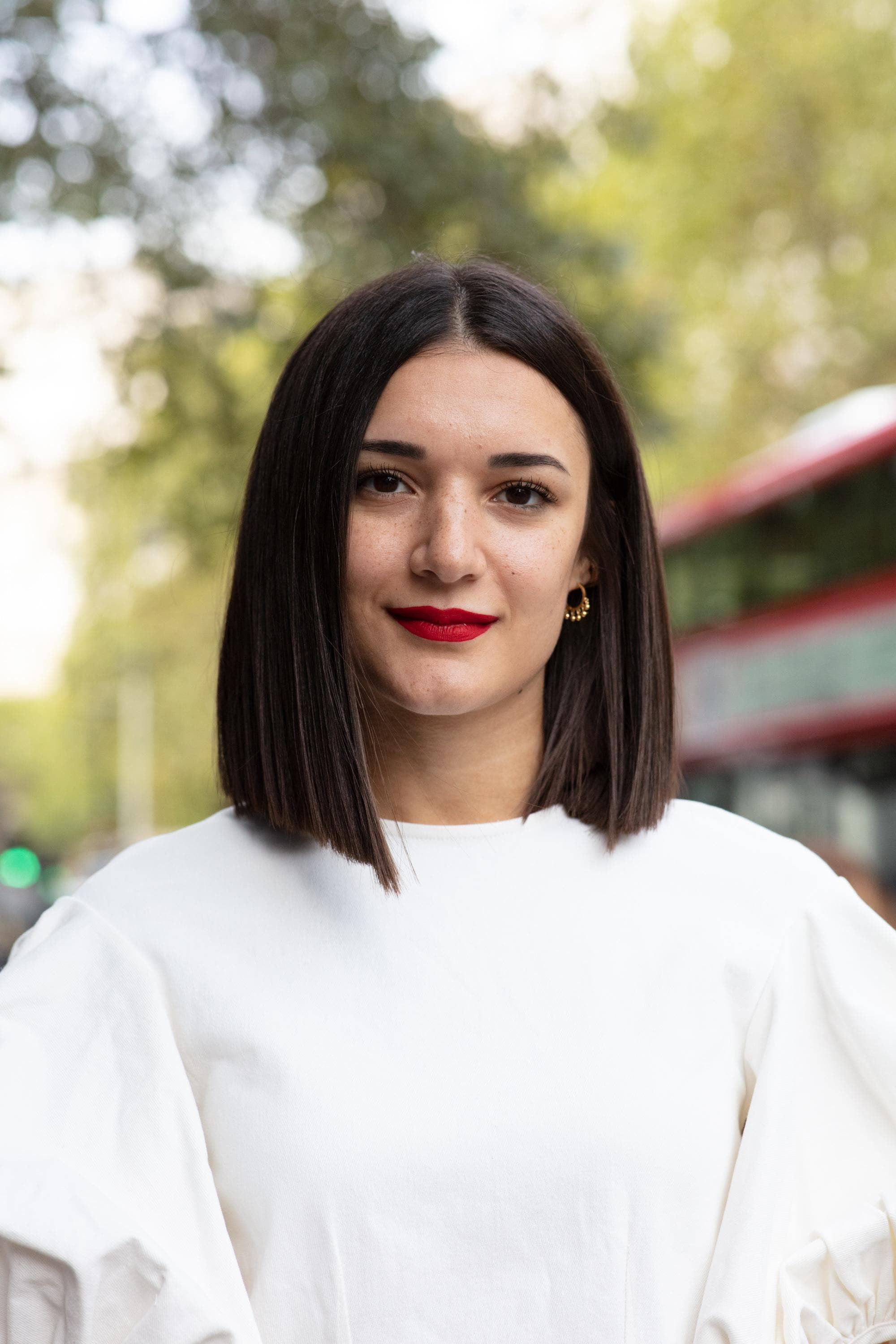 London Fashion Week street style hair: Close up shot of a woman with a sleek, dark chocolate blunt cut long bob wearing a white jumper and posing on the street