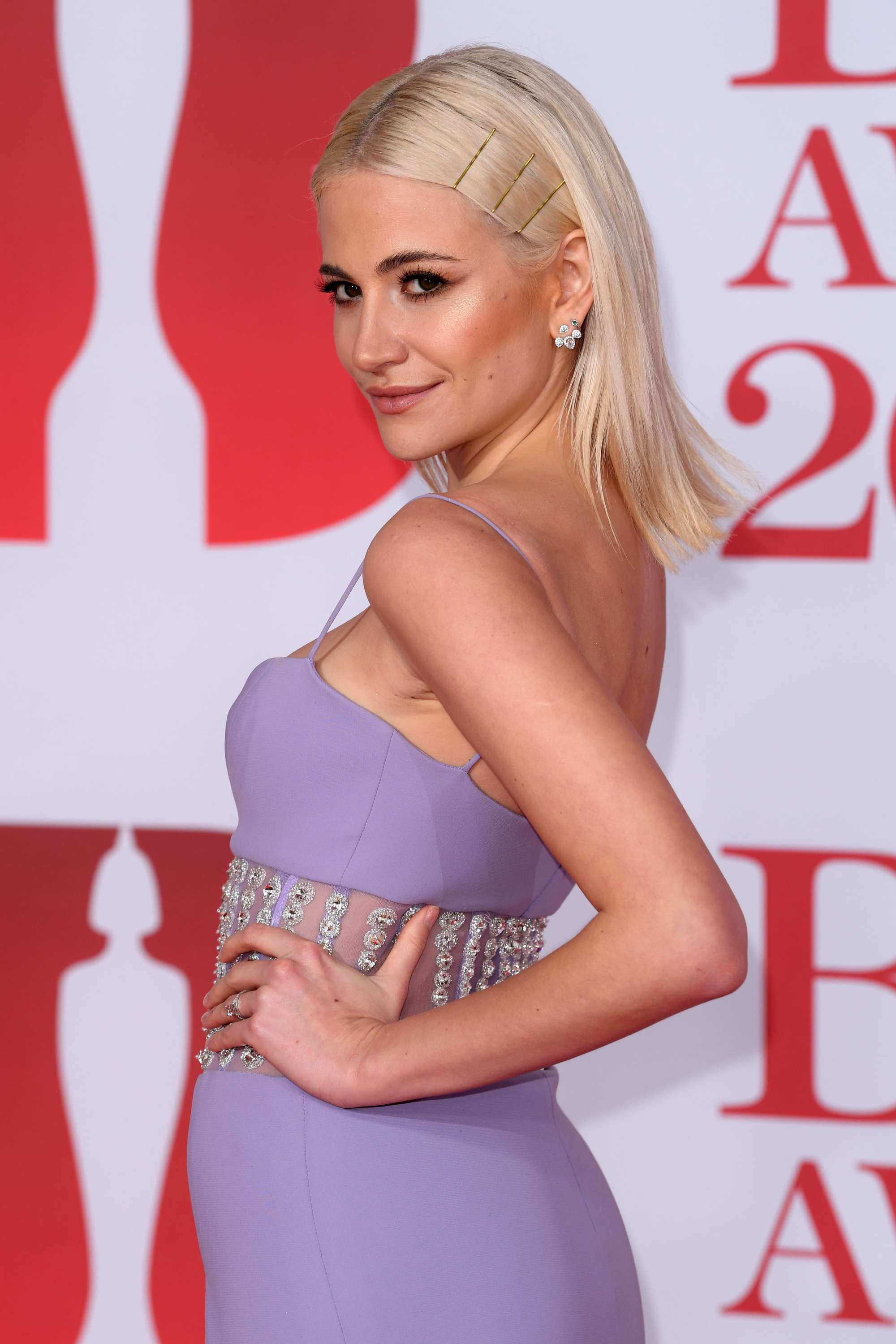 close up shot of pixie lott with sleek blonde hair with bobby pins in it, wearing lilac dress and posing on the brit awards 2018 red carpet
