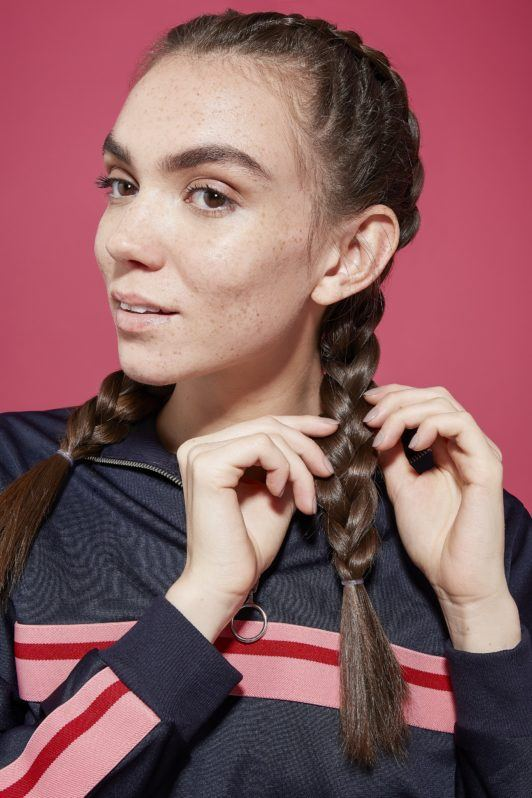 Brunette woman pulling on boxer braid from opposite sides