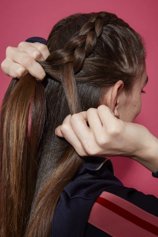 Brunette girl showing back of head boxer braid in process