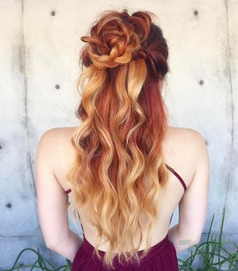woman with ombre red to strawberry blonde long curly hair in a braided flower bun half-up style