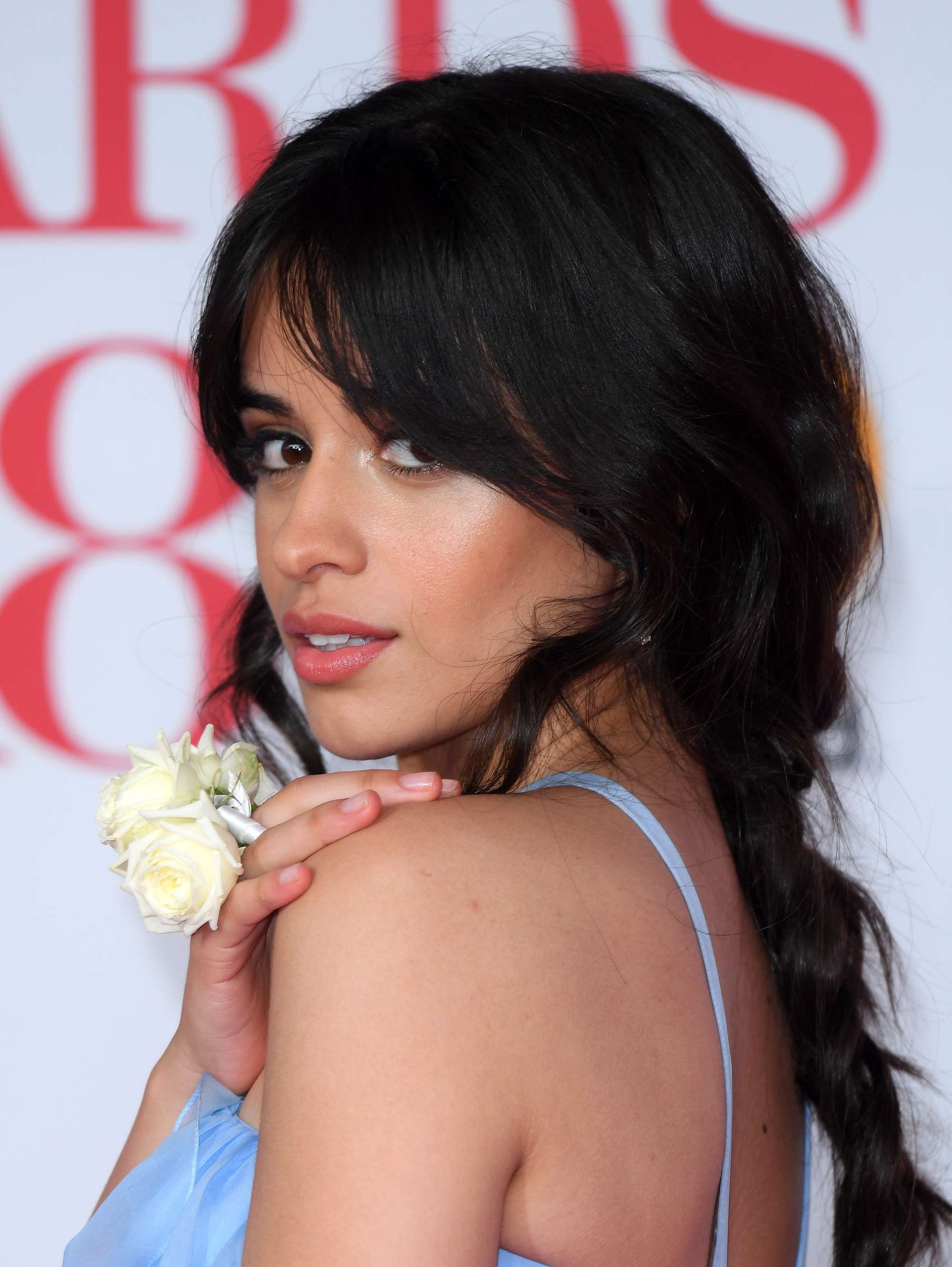close up shot of camila cabello with braided ponytail and split bangs, wearing blue and white flower accessory on the brit awards red carpet 2018