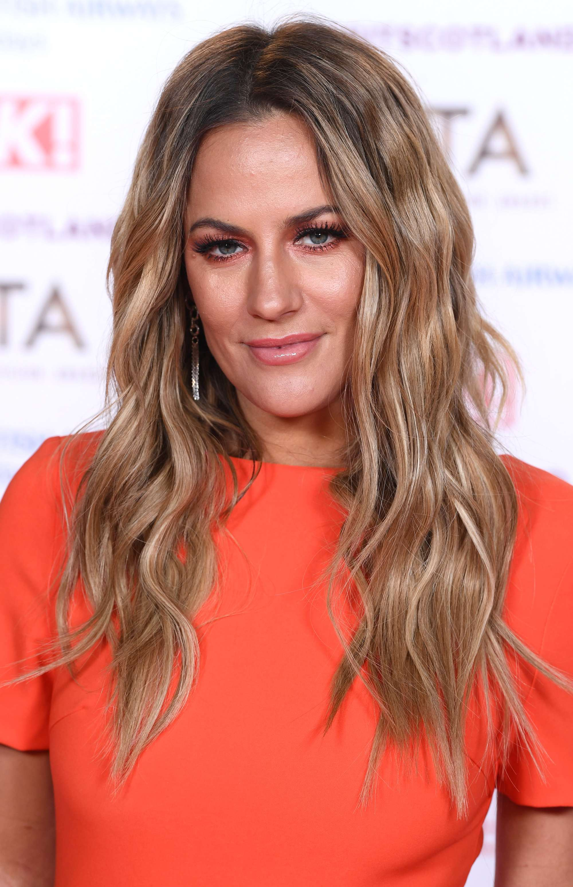 Brown hair with blonde highlights: Caroline Flack with long wavy brown hair with highlights, wearing an orange dress