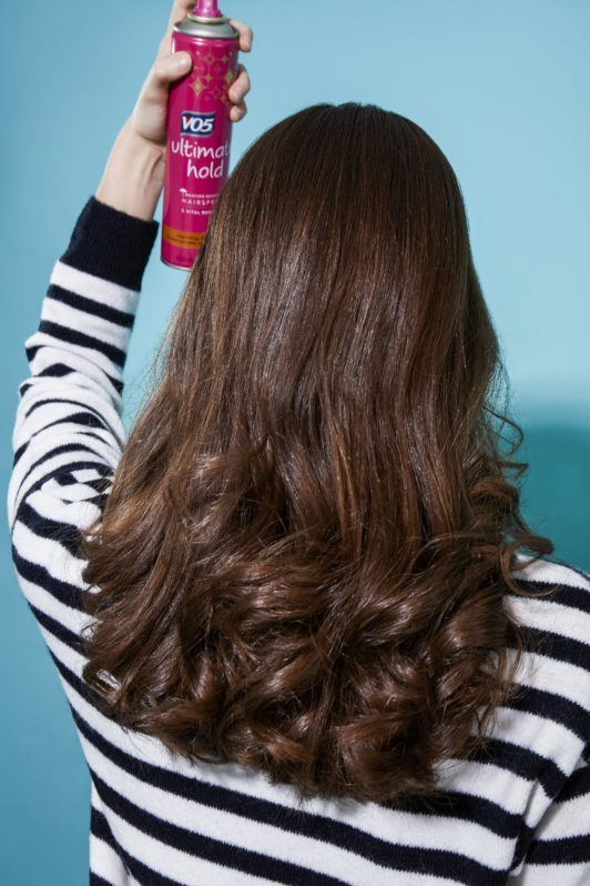 Brunette girl spraying hairspray on the back of her head with headband curls