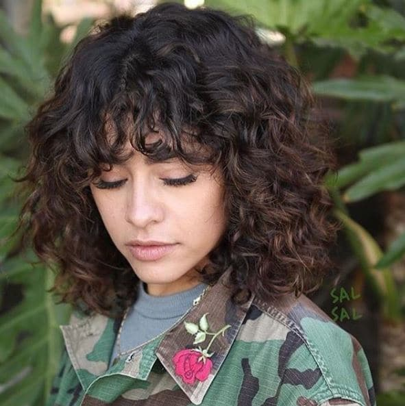 woman with brown curly shag long bob with bangs