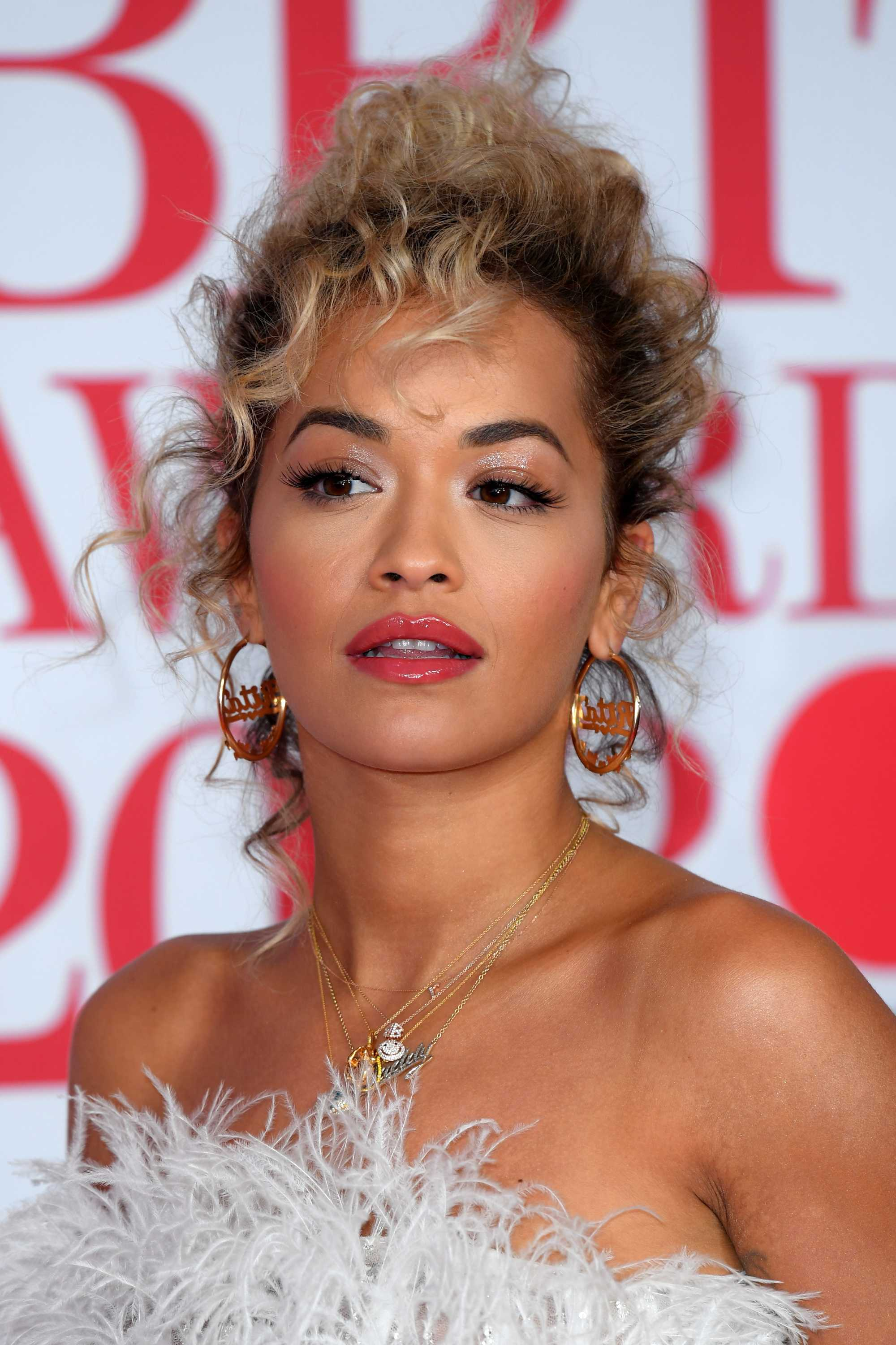 close up shot of rita ora with curly updo hairstyle, wearing hoop earrings and white frilly dress on the brit awards 2018 red carpet