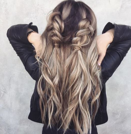 Second day hair: Woman with long dark ash blonde hair in half-up double dutch braids wearing black jacket