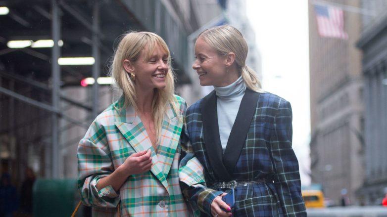Two blonde street stylers at fashion week walking down the street