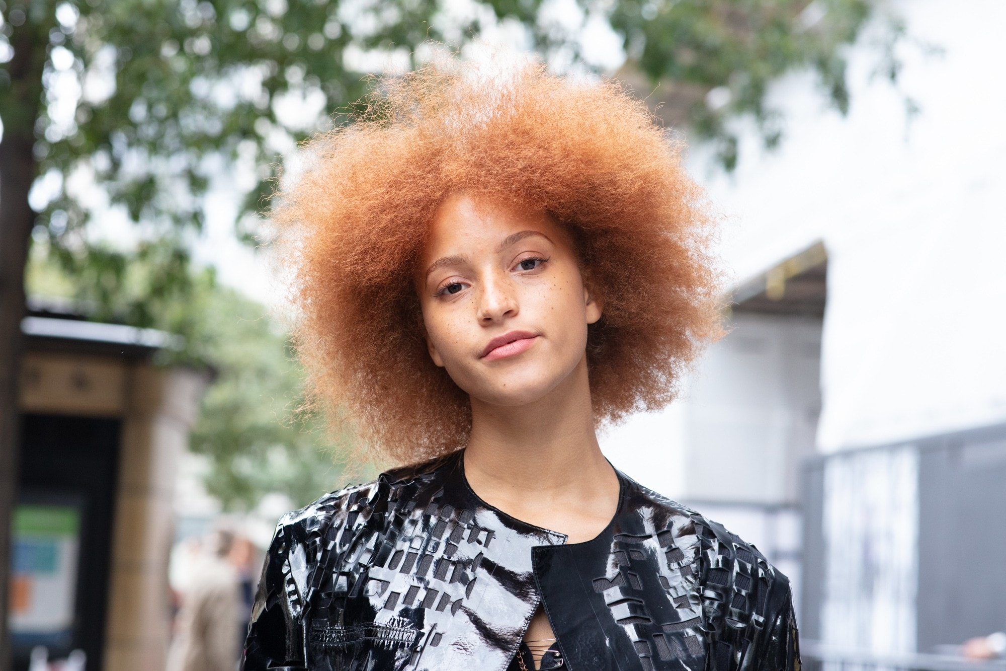 London Fashion Week street style hair: Close up shot of a woman with a ginger, fluffed out medium afro wearing a printed shirt and posing on the street