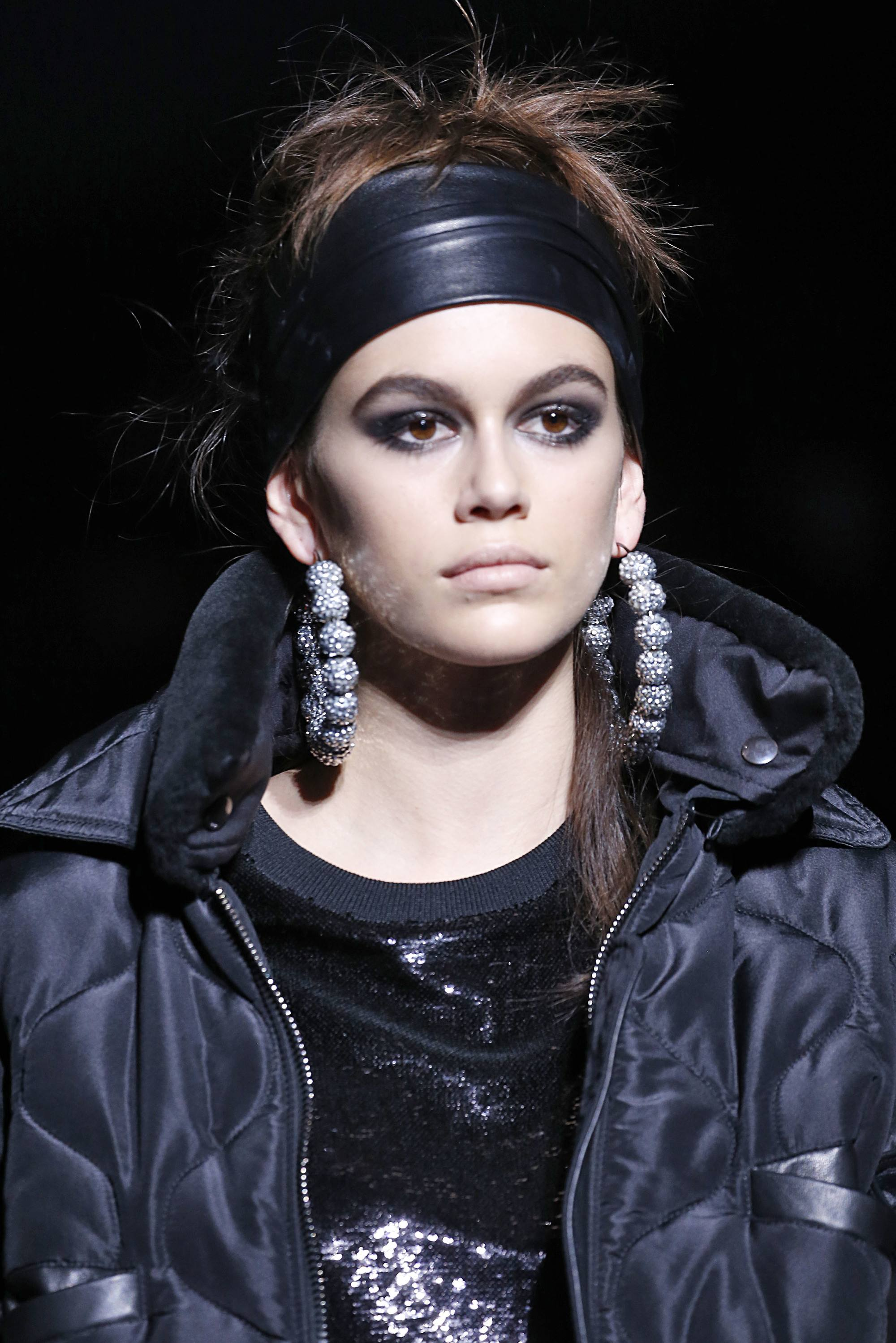 kaia gerber on tom ford runway with brown hair in updo with large black leather headband and large hoop earrings