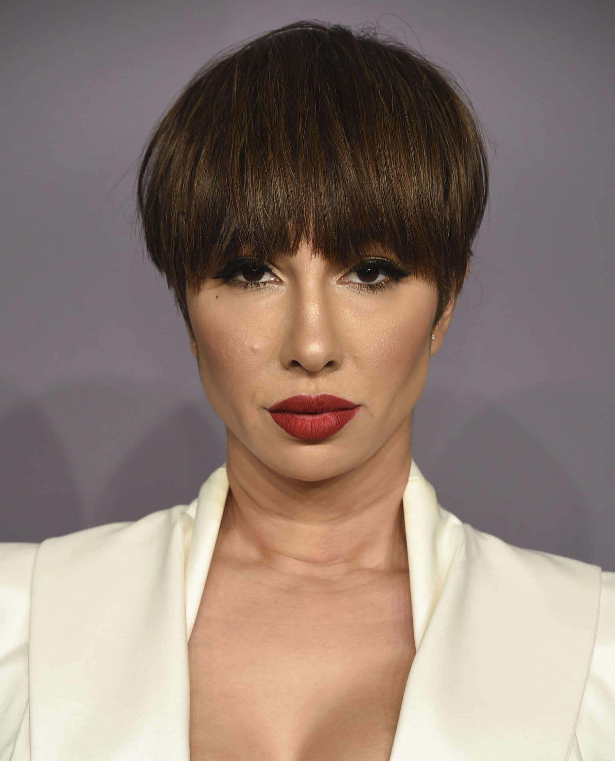 close up shot of jackie cruz with thick bangs and pixie haircut, wearing all white and red lipstick