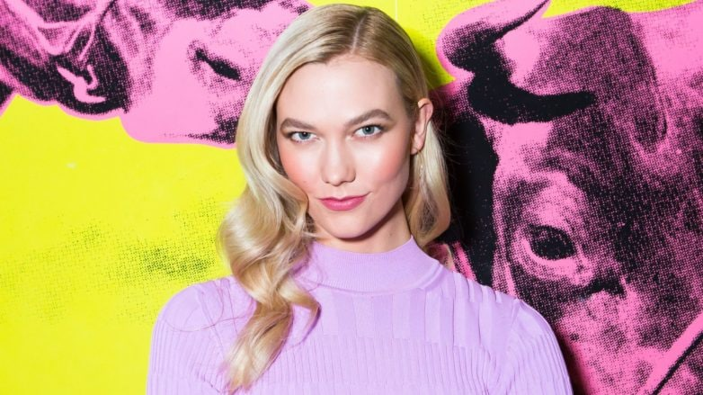 best conditioner for fine hair: close up shot of karlie kloss with wavy hair, wearing lilac jumper and posing at carolina herrera fashion show