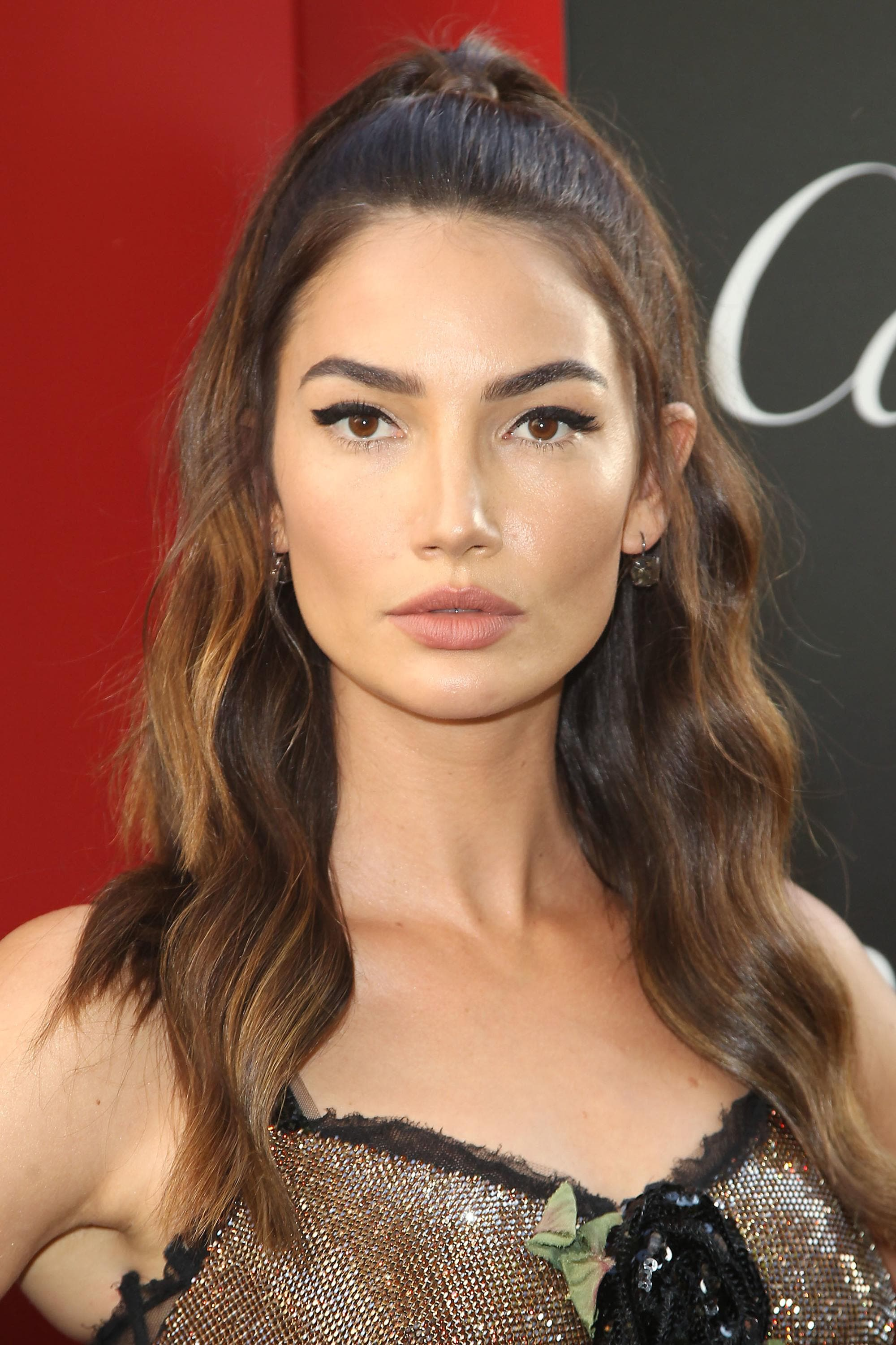 Brown hair with blonde highlights: Lily Aldridge with chocolate brown hair with blonde balayage, styled in a half up half down ponytail with waves