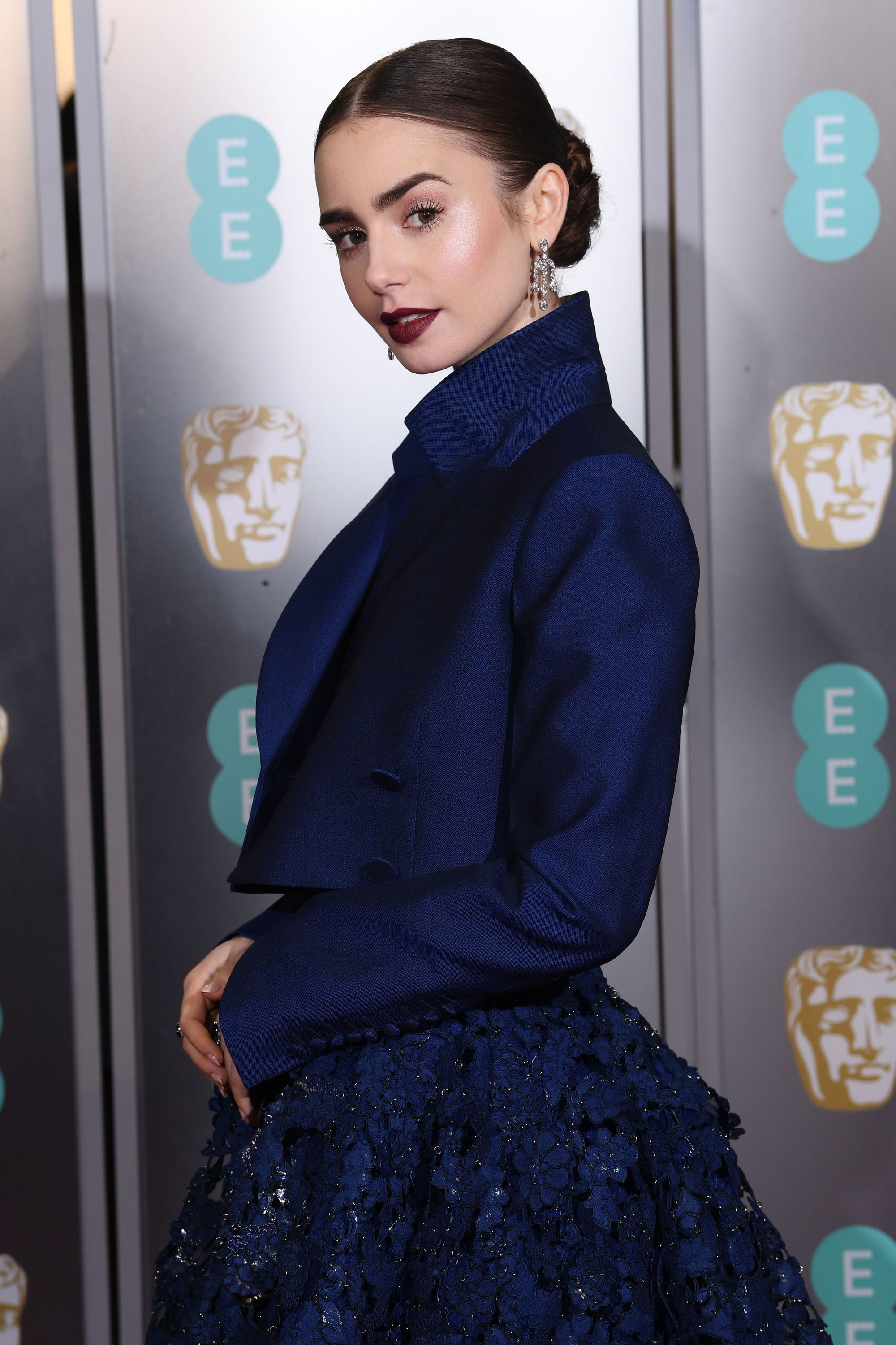 BAFTAs hairstyles: Lily Collins with dark brown hair in smooth low bun with dark lipstick on red carpet 2019.