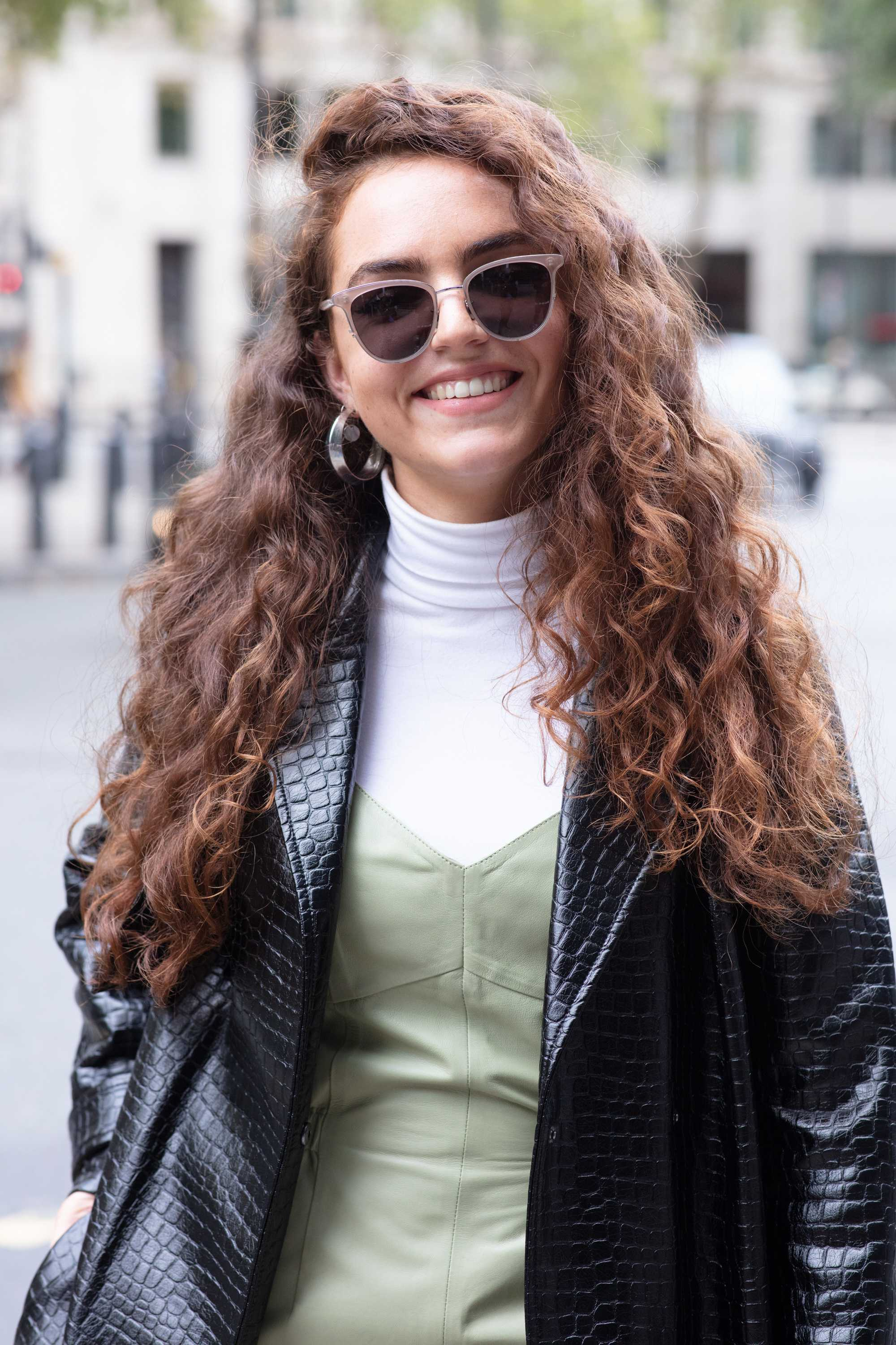 London Fashion Week street style hair: Close up shot of a woman with long chestnut brown big curls, wearing sunglasses and leather jacket on the street