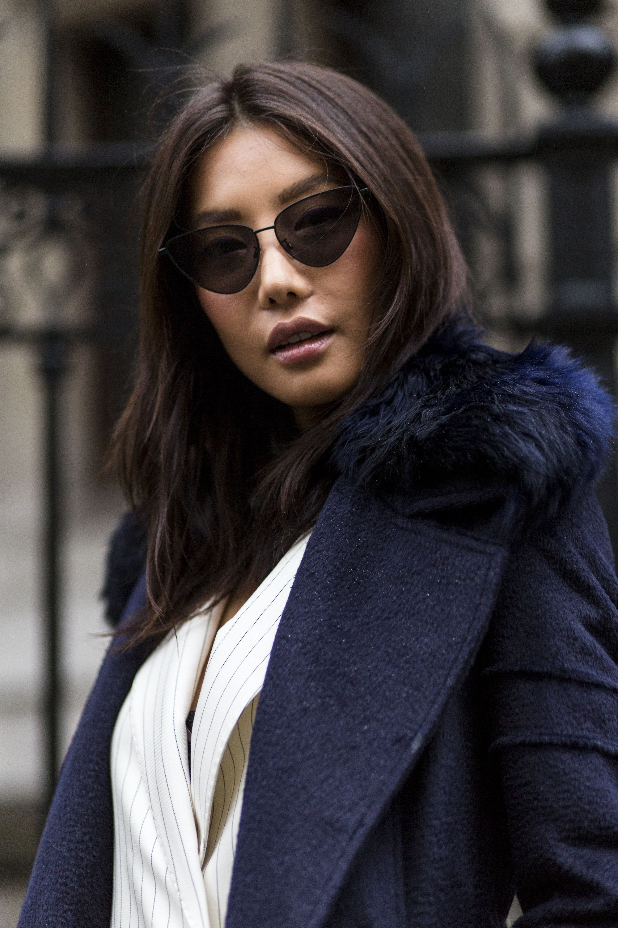 close up shot of woman with loose waves hair, wearing blue jacket and white shirt and posing at london fashion week 2018