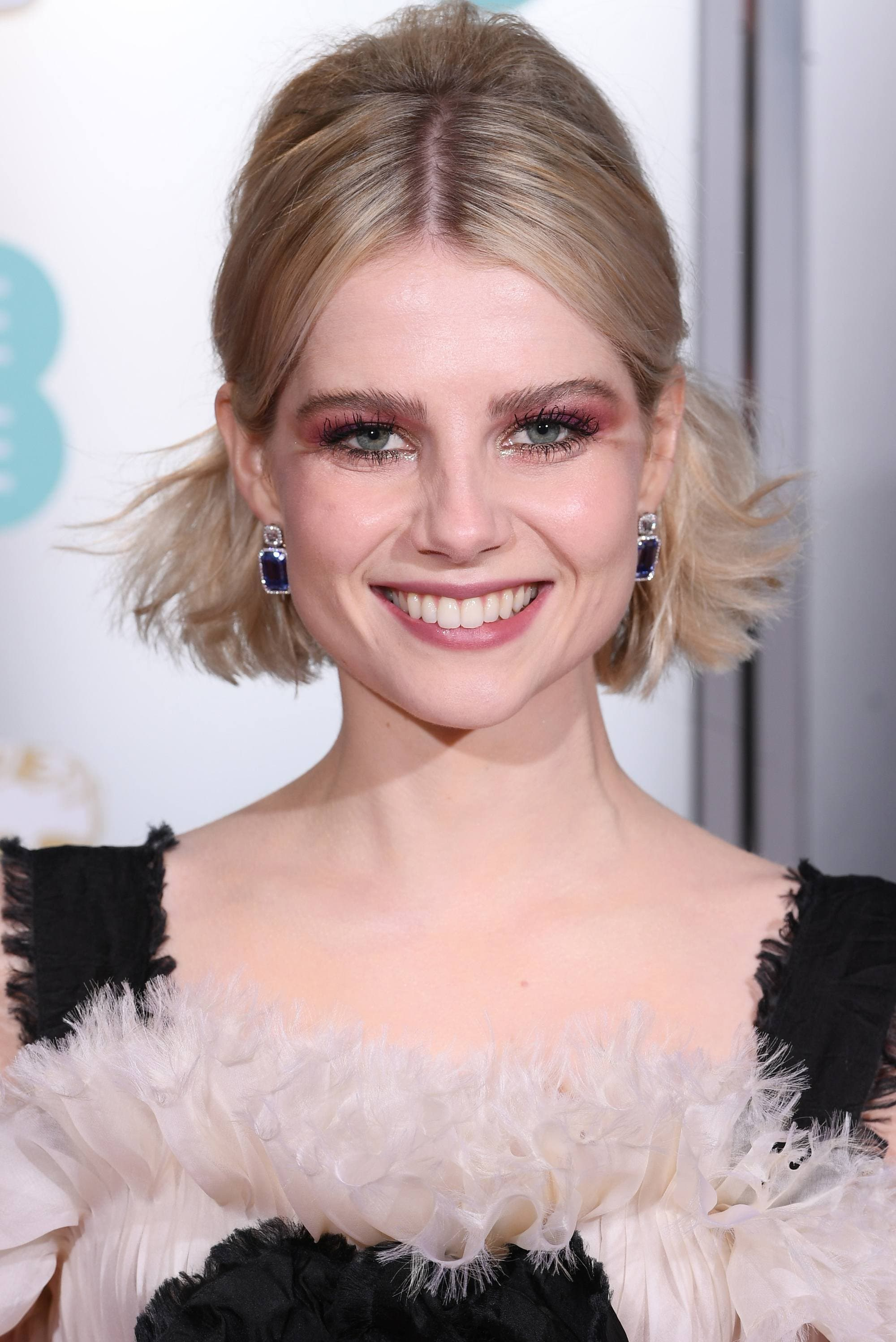 BAFTAs hairstyles: Lucy Boynton with blonde bob styled in a half-up, half-down pinned back hairstyle with volume at the crown on the red carpet.