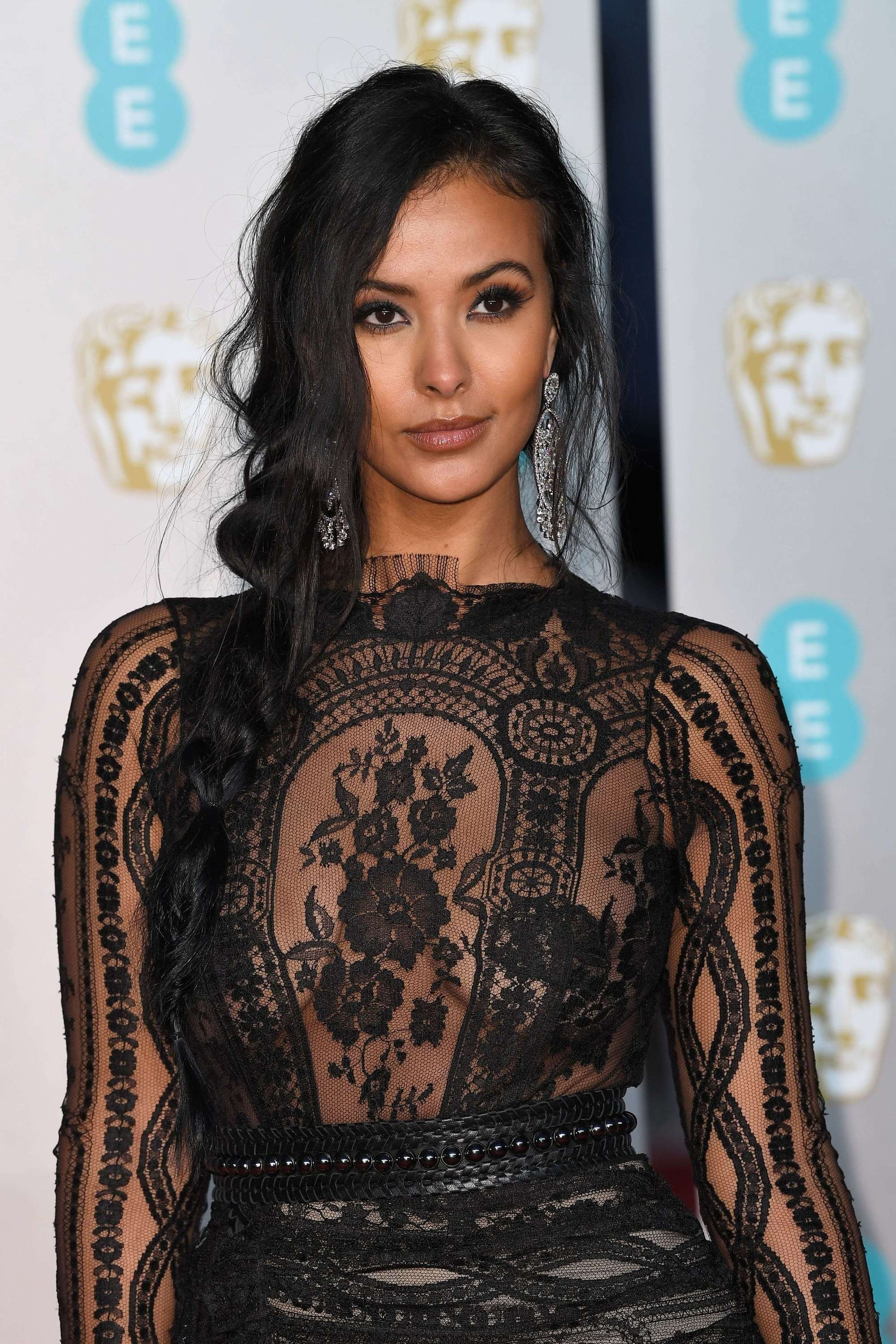 BAFTAs hairstyles: Maya Jama with long wavy dark brown hair styled in a side rope twist wearing a black sheer dress.