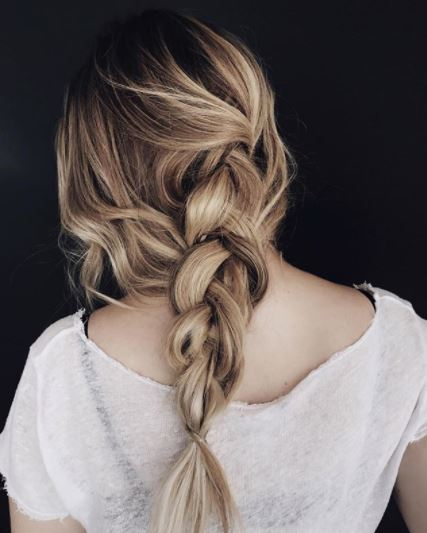 Second day hair: Woman with dark blonde hair in braid wearing white top