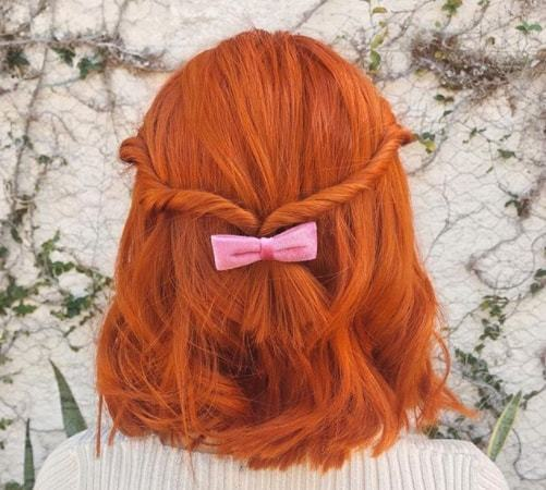 short red hairstyles: close up shot of woman with ginger hair styled into a half up half down twisted style with bow
