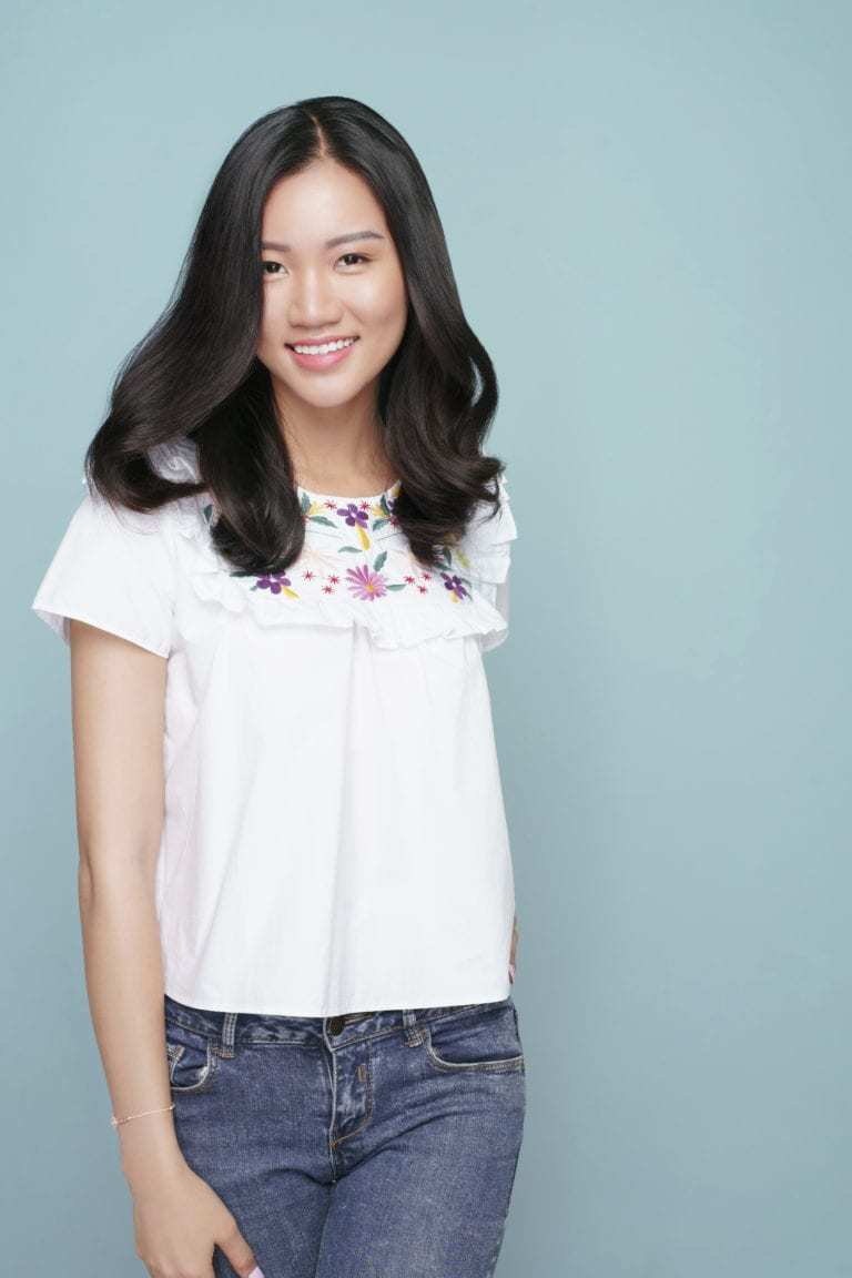 Asian hairstyles: Asian woman with long wavy blowout brown hair wearing a white top and jeans.