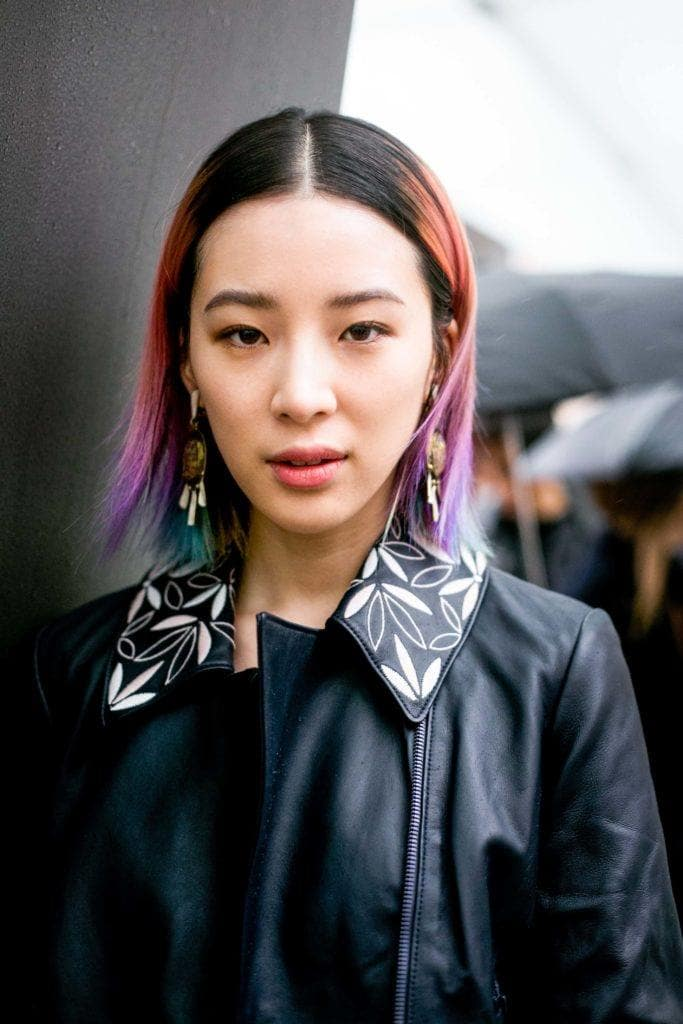 Asian hairstyles: Asian woman with straight multi-coloured long bob wearing a leather jacket.