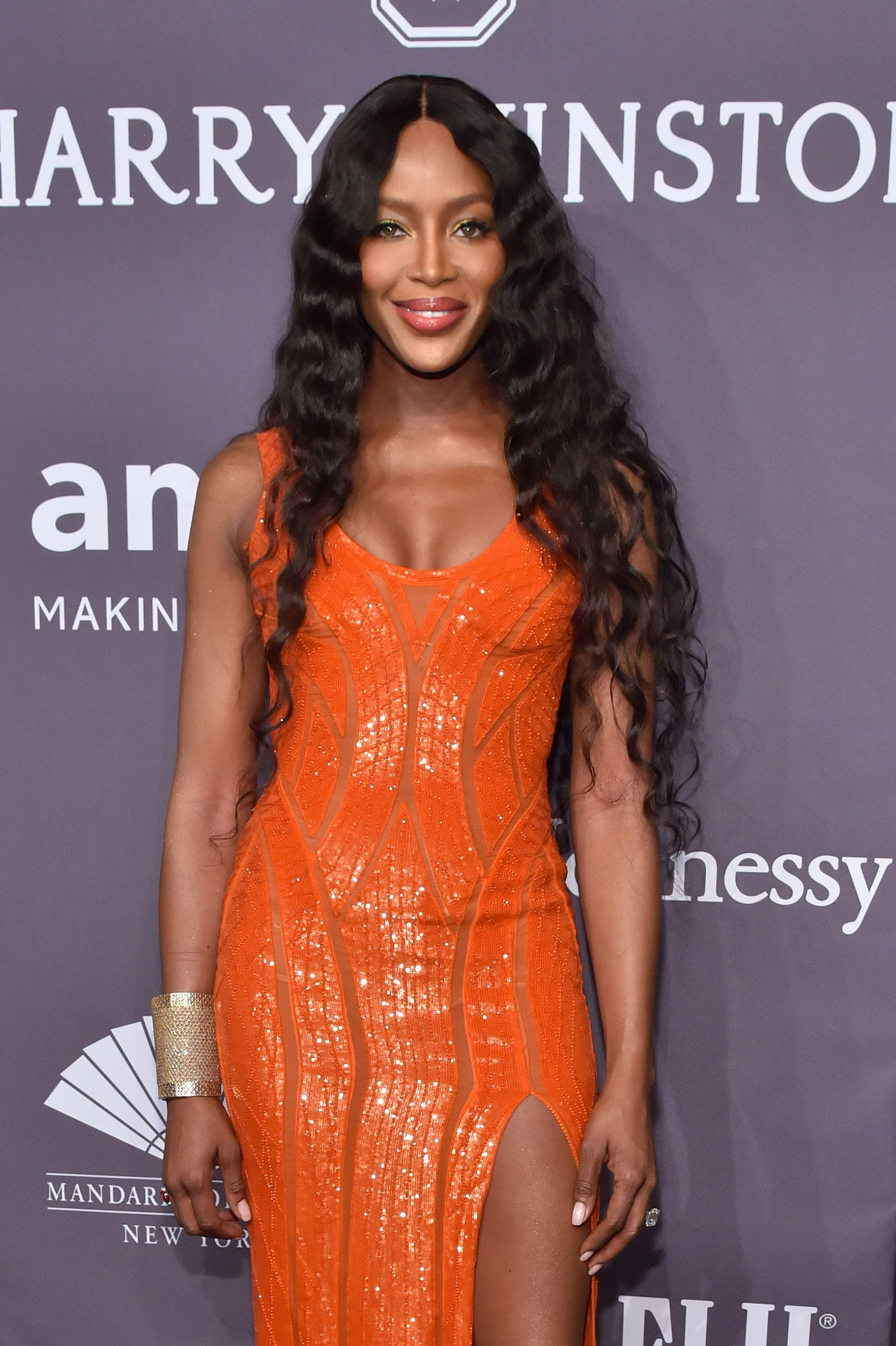 Naomi Campbell in orange dress at AmfAR gala with long curly hair what is a weave