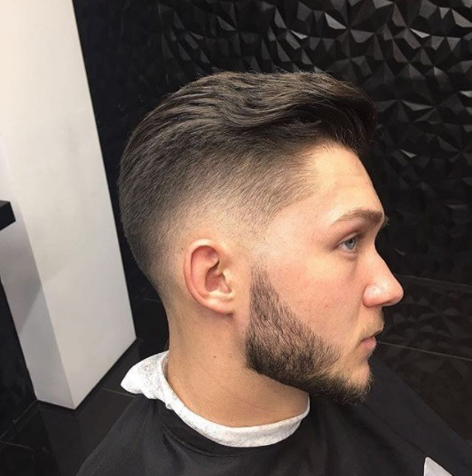 man with brown hair in the barbers with a black cape wrapped around him and his hair in a wavy styled neat pompadour fade