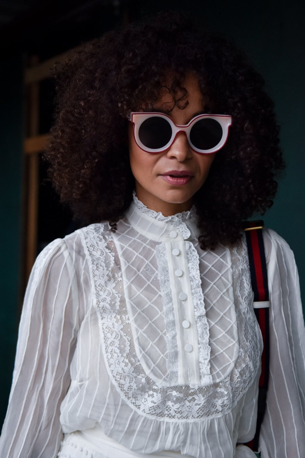 NYFW SS19 street style: Natural haired street styler wearing a high neck victoriana shirt and circle sunglasses