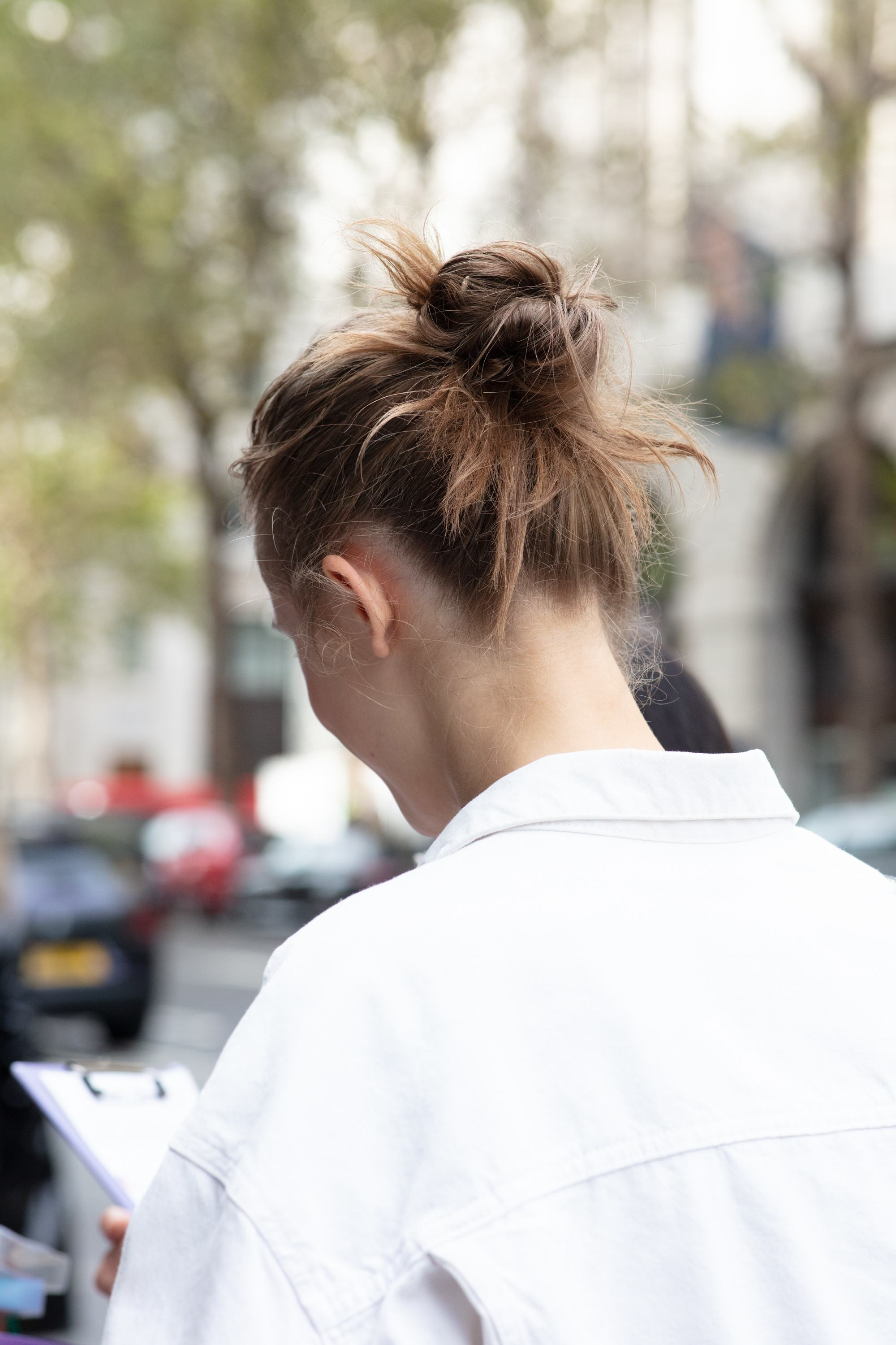 London Fashion Week street style hair: Close up shot of a woman with medium brown hair styled into a messy bun with loose strands sticking out to resemble an octopus, wearing white and posing for a photo