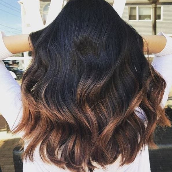 back view of long dark brown wavy hair with ombre finish