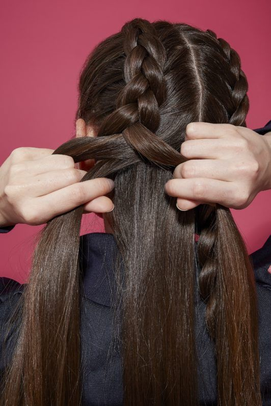 Brunette woman plaiting a boxer braid into hair with back to the camera