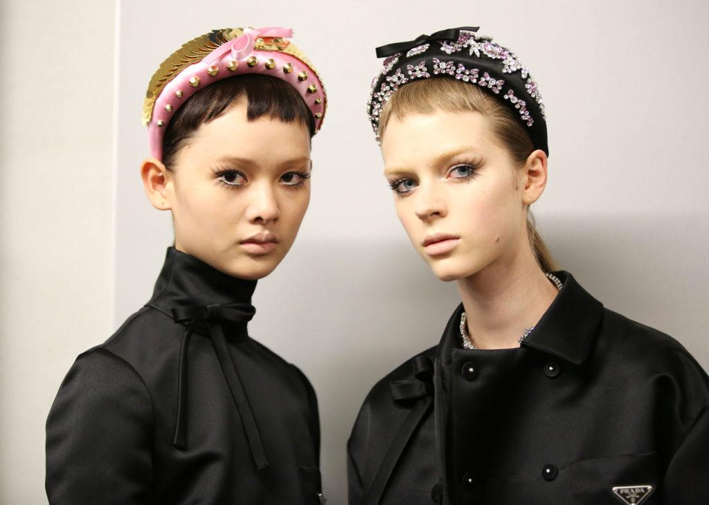 Milan Fashion Week SS19: Two models at Prada, one with a short dark pixie cut and one with a blonde pixie, both wearing oversized satin headbands and short micro bangs
