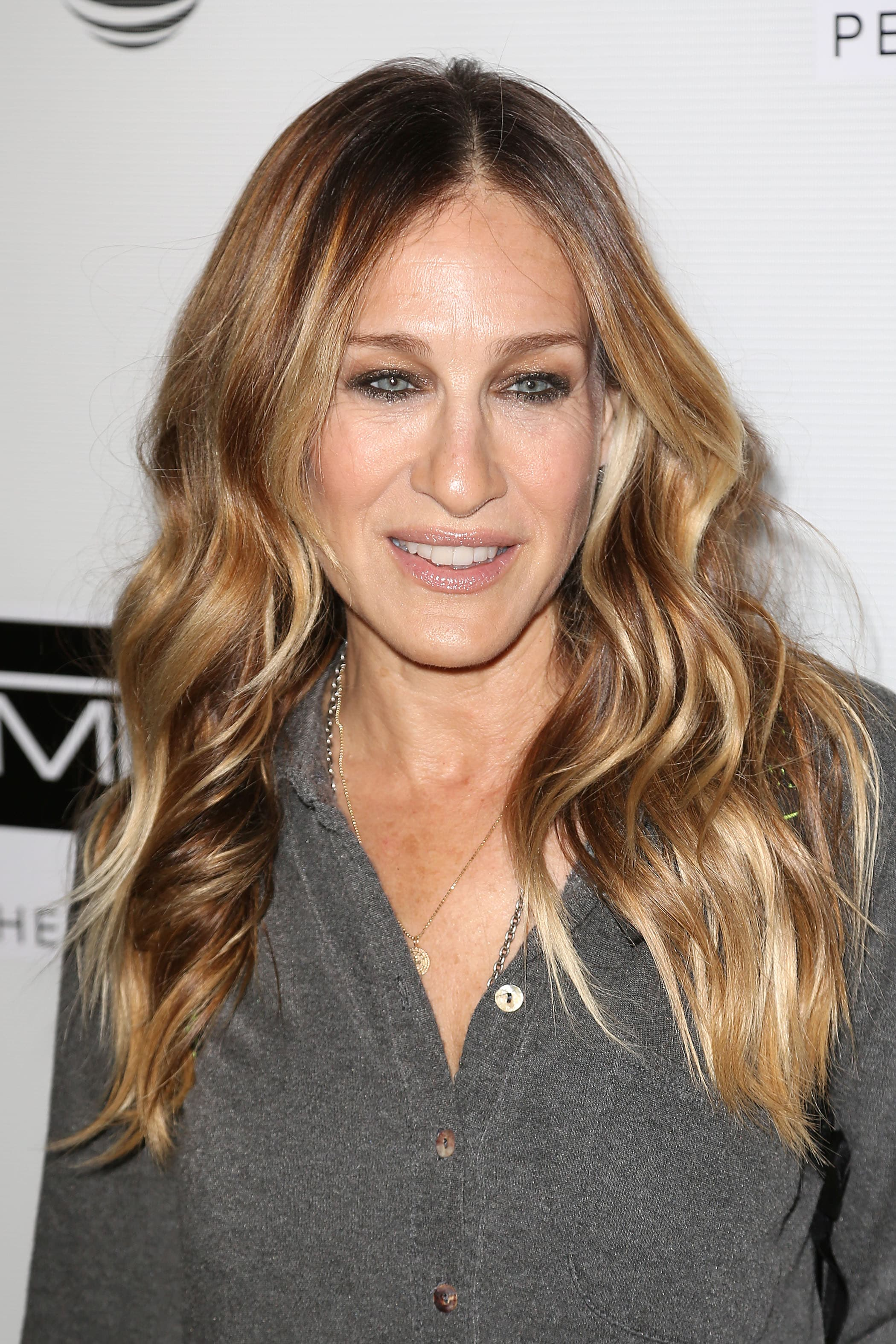 Brown hair with blonde highlights: Sarah Jessica Parker with long wavy bronde hair with highlights, wearing a grey shirt