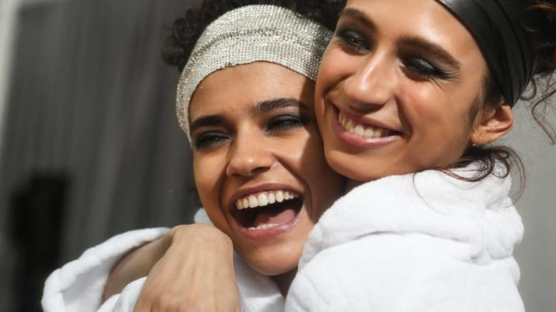 models backstage at Tom Ford fashion show wearing white gown and headbands