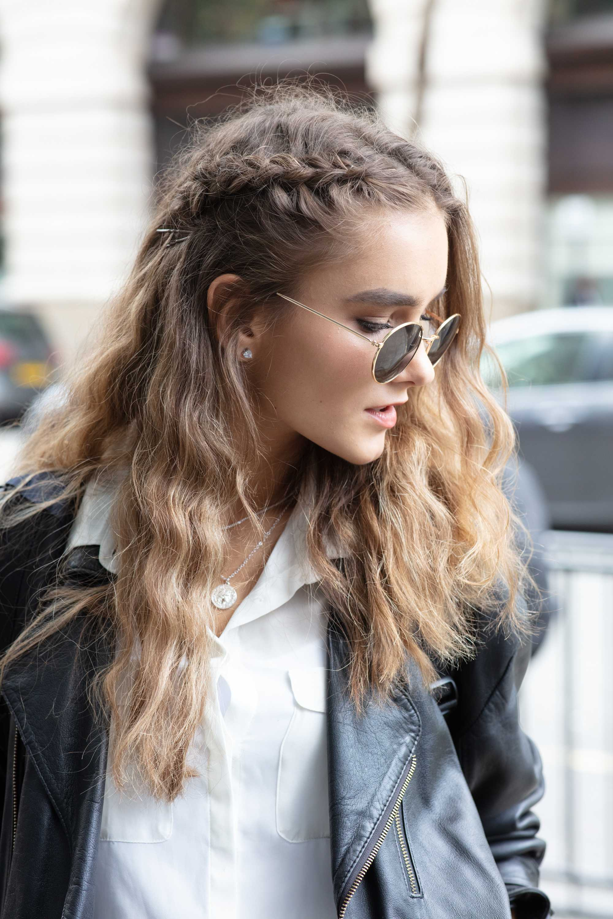 London Fashion Week street style hair: Close up shot of a woman with light brown long hair styled into waves with a side plait, wearing sunglasses and leather jacket and posing on the street