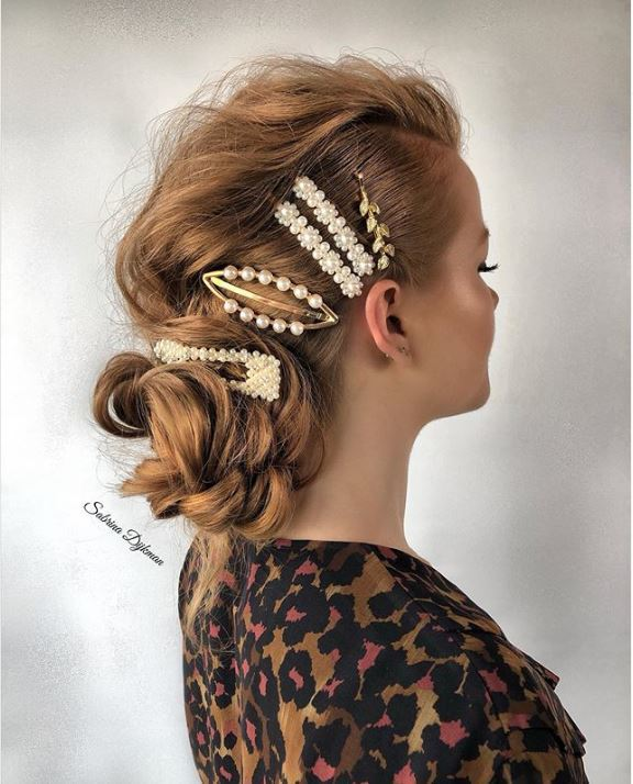 Woman with blonde hair in side bun with stacked hair clips