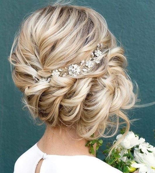back view of blonde woman with pinned side bun hairstyle with floral accessories holding flowers