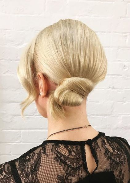 back view of woman with light blonde hair in smooth side bun with black lace top