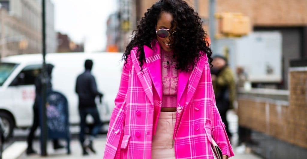 Black girl with curly hair walking outside fashion week show
