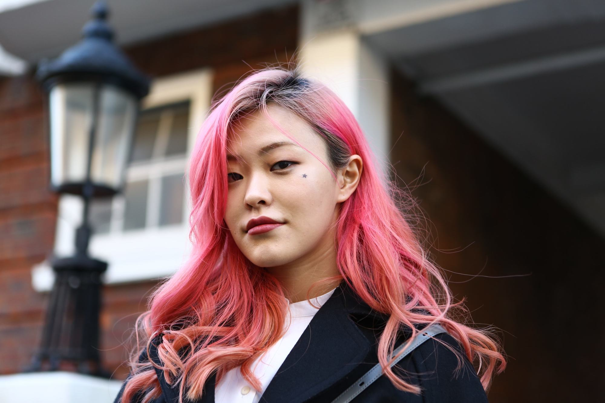 Asian girl with dyed pink hair standing outside