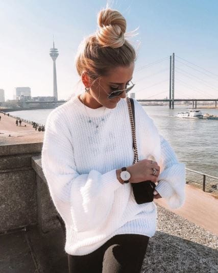 Second day hair: Woman with blonde hair in high top knot updo wearing big white jumper